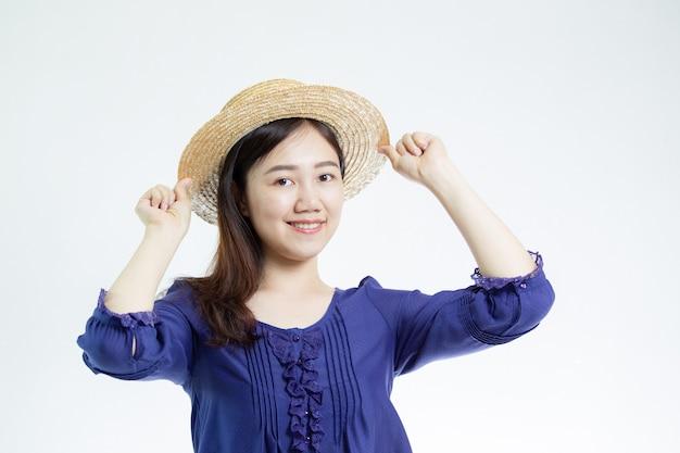 Jolie femme asiatique coiffé d'un portrait de chapeau se bouchent sur blanc avec fond.