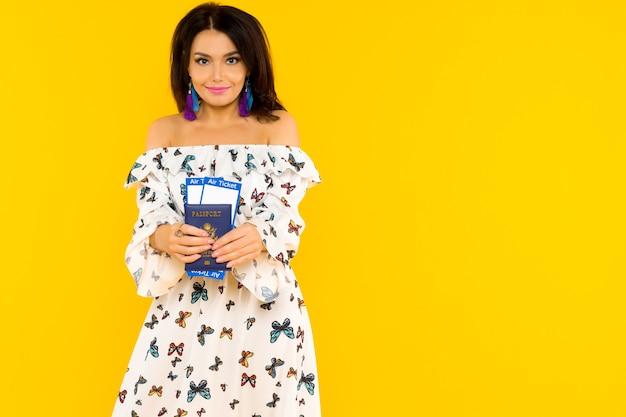 Une jolie femme asiatique dans une robe en soie avec des papillons tient un passeport