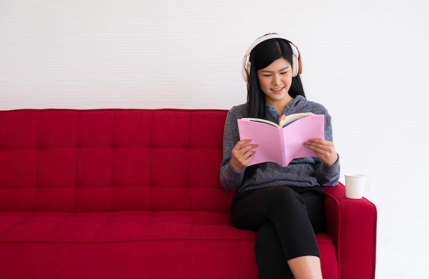 Jolie femme asiatique est assise sur le canapé le matin et lisant un livre