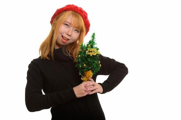 Jolie femme asiatique heureuse souriant tout en tenant l'arbre de bonne année