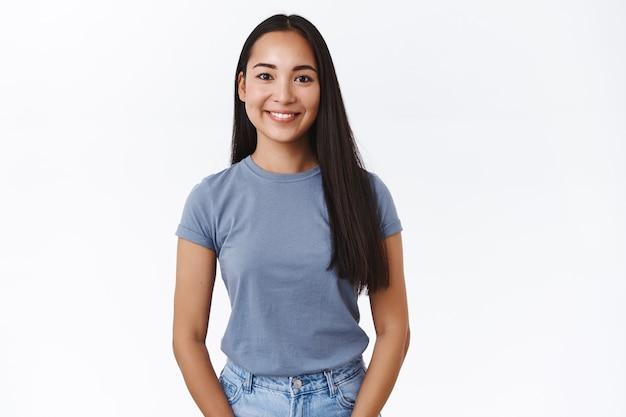Jolie femme asiatique moderne aux longs cheveux noirs souriante heureuse et regardant la caméra, pose décontractée debout, pensant à la fête de noël à venir, exprime des émotions positives et joyeuses, mur blanc