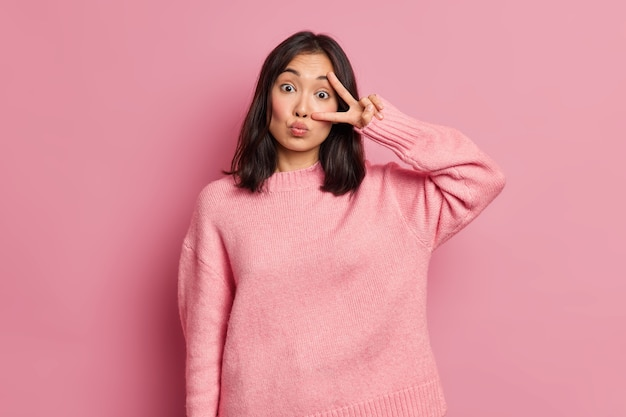 Jolie femme asiatique montre le signe de la victoire sur les yeux garde les lèvres arrondies fait un geste disco s'amuse à l'intérieur porte un pull décontracté