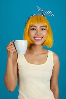 Jolie femme asiatique en perruque lumineuse, buvant du café du matin