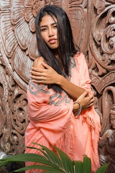 Jolie femme asiatique en robe ethnique boho posant sur un mur ornemental en bois.