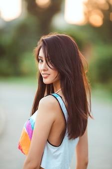 Jolie femme asiatique sexy sportive en vêtements décontractés debout avec dans le parc de la ville. l'été de la mer
