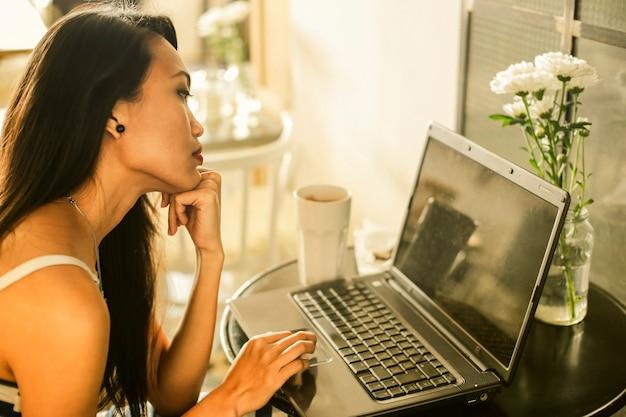 Jolie femme asiatique travaillant sur un ordinateur portable