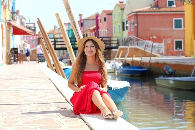 Jolie femme assise au bord du canal de venise dans le village de burano, italie