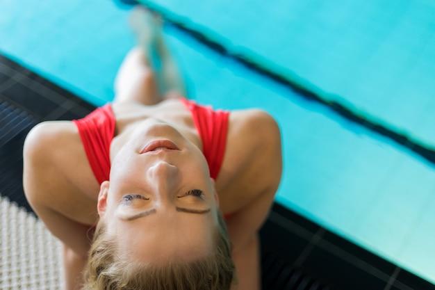 Jolie femme assise au bord d'une piscine