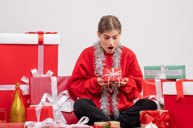 Jolie femme assise autour de cadeaux de noël sur blanc