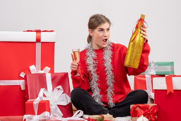 Jolie femme assise autour des cadeaux de noël célébrant avec du champagne sur blanc