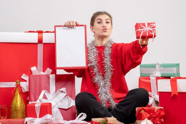 Jolie femme assise autour des cadeaux de noël avec note sur blanc
