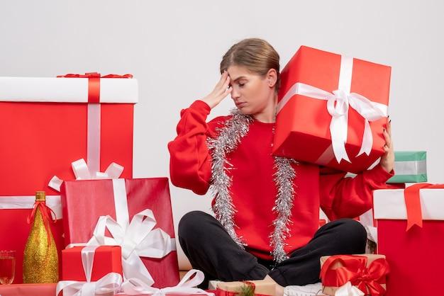 Jolie femme assise autour des cadeaux de noël se sentant stressée sur blanc