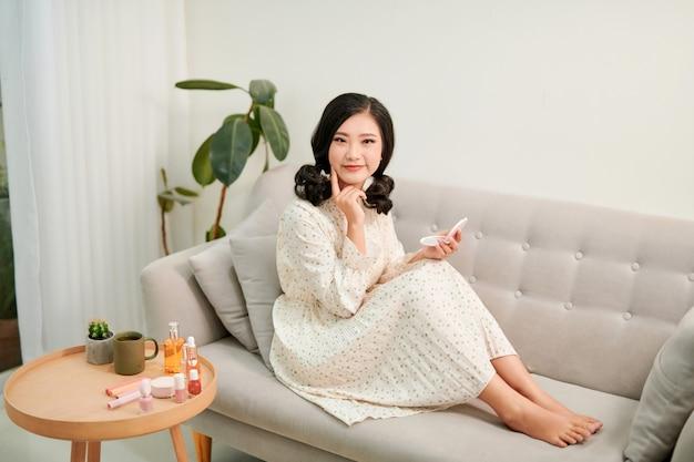 Jolie femme assise sur le canapé a l'air heureuse et calme. concept de beauté, soins personnels, cosmétiques, jeunesse, week-end à la maison, spa.