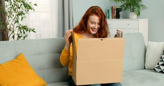 Jolie femme assise sur un canapé dans le salon et l'ouverture de la boîte en carton