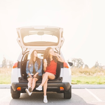 Jolie femme assise sur le coffre de la voiture