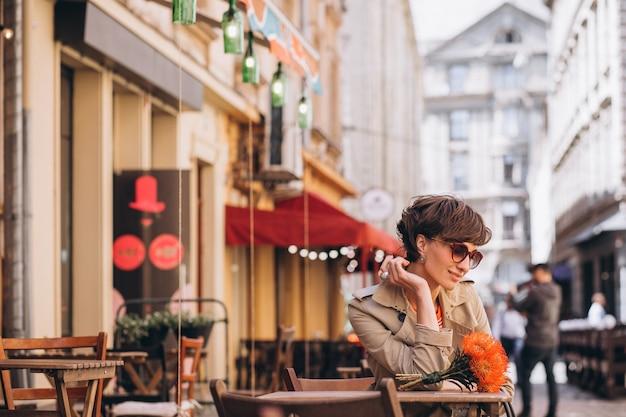 Jolie femme assise dans un café dans la ville chinoise
