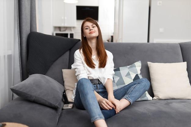 Jolie femme assise dans un canapé confortable et intérieur au repos