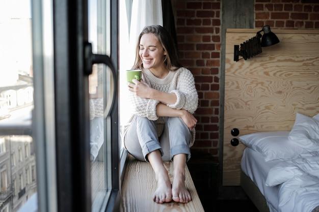 Jolie femme assise dans le rebord de la fenêtre