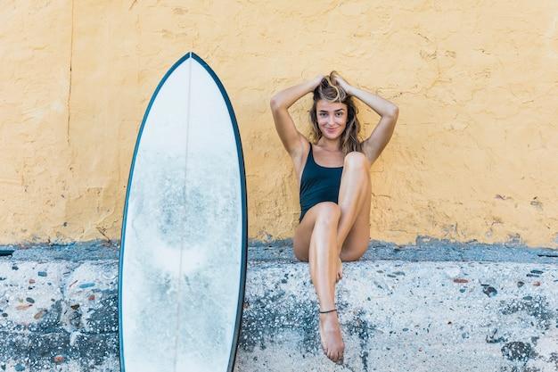 Jolie femme assise avec planche de surf s'appuyant sur le mur