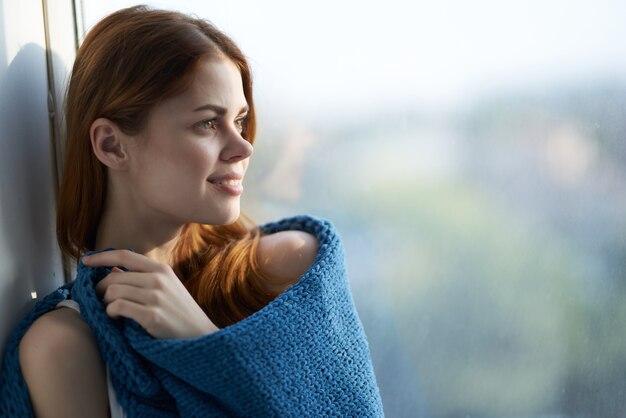 Jolie femme assise près de la fenêtre avec un plaid bleu. photo de haute qualité