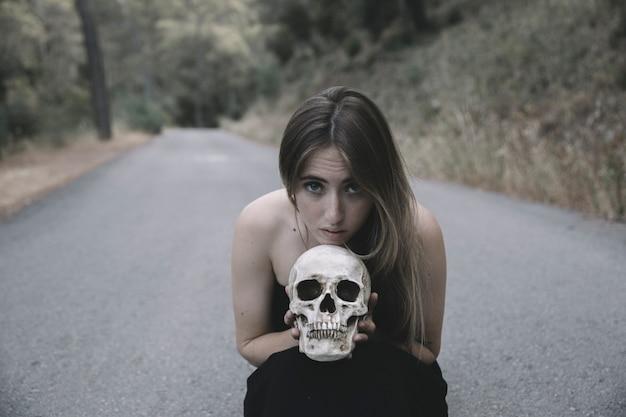 Jolie femme assise sur la route et regardant la caméra tenant un crâne décoratif de l'homme