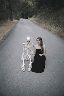 Jolie femme assise sur la route avec un squelette décoratif humain et regardant la caméra