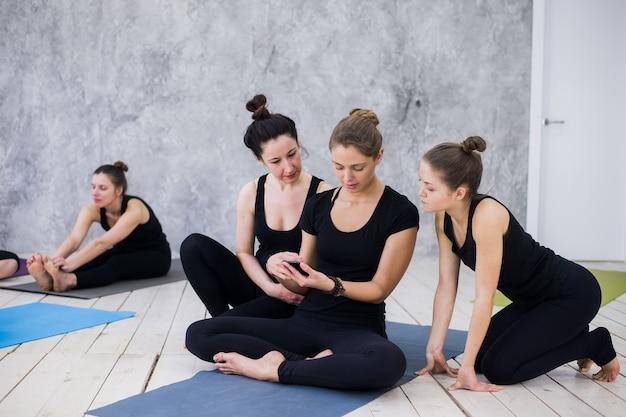 Jolie femme assise et socialisant avec le groupe après leur cours de yoga