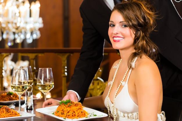 Jolie femme assise à une table dans un restaurant gastronomique, le serveur a servi le dîner, un grand lustre est en