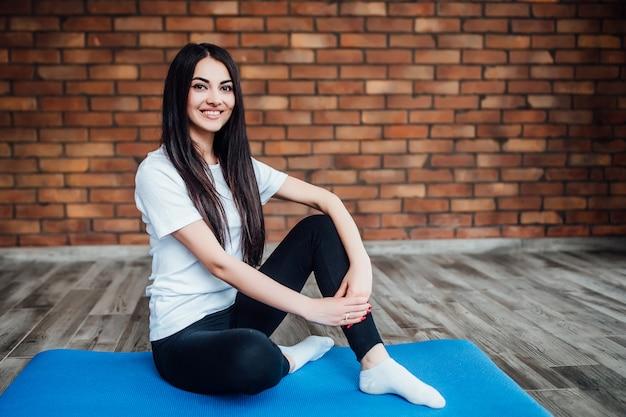 Jolie femme assise sur un tapis bleu à la maison et prépare le renforcement.