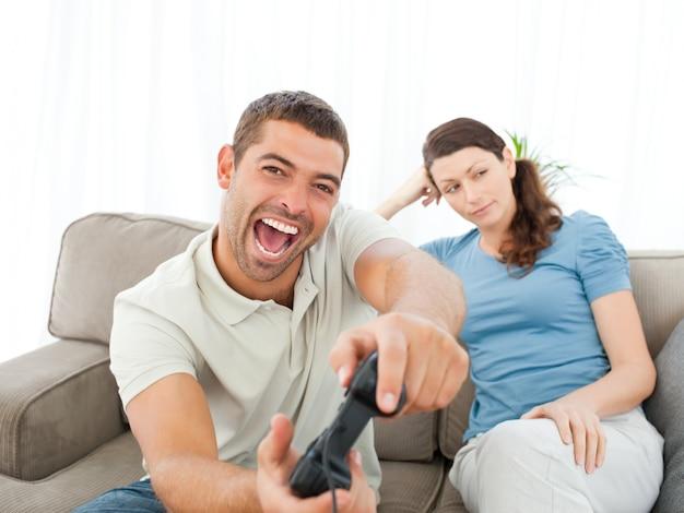 Jolie femme attend son garçon jouant à des jeux vidéo sur le canapé