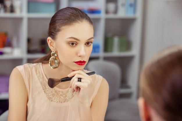 Jolie femme attirante regardant son visage tout en tenant un pinceau de maquillage