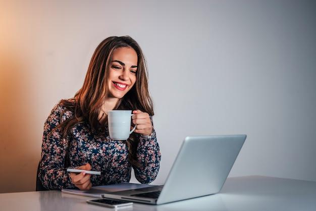 Jolie femme au bureau regardant un ordinateur portable et prenant des notes.