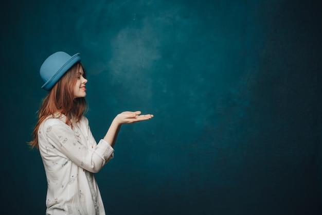 Jolie femme au chapeau bleu montre avec sa main sur le côté sur une sombre