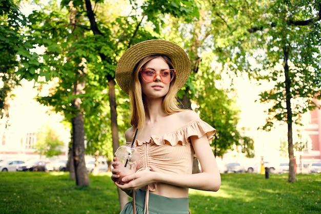 Jolie femme au chapeau dans le parc boire des verts de repos