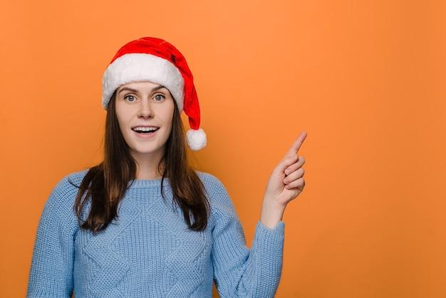 Jolie femme au chapeau rouge pointe le doigt avant à droite