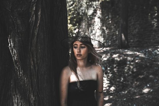 Jolie femme au chapeau de sorcière à côté de l'arbre et regardant ailleurs