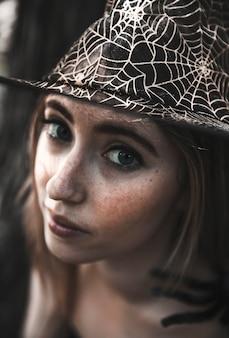 Jolie femme au chapeau de toile d'araignée décorative regardant la caméra