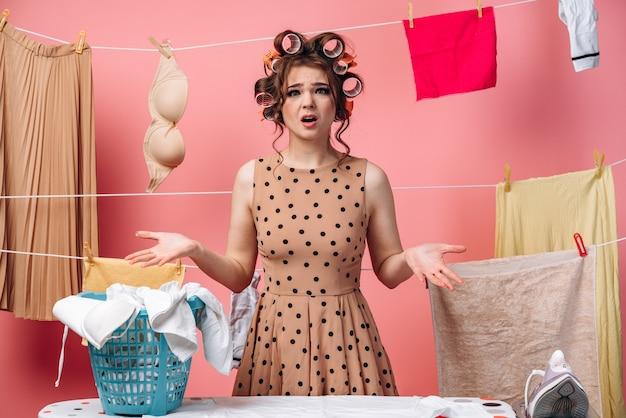 Une jolie femme au foyer avec des bigoudis est choquée par la quantité de travail à faire dans la maison. concept de ménage.
