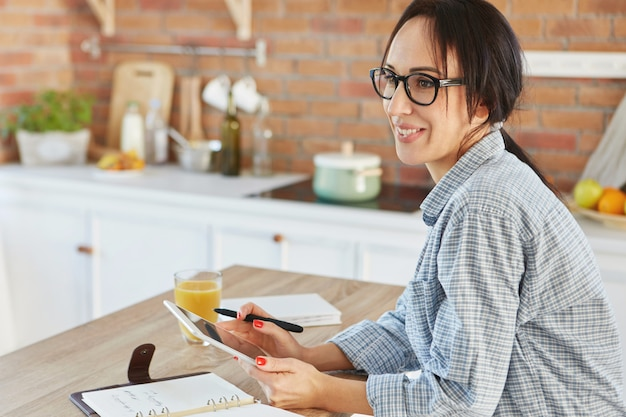 Jolie femme au foyer étant seule à la cuisine, détient une tablette moderne,