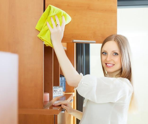 Jolie femme au foyer, nettoyer les meubles avec du chiffon
