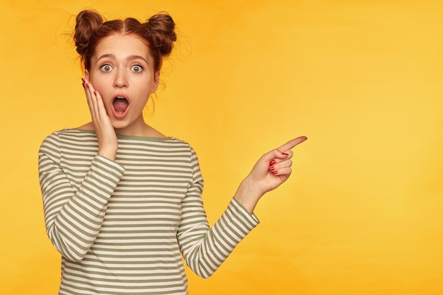 Jolie femme au gingembre avec deux petits pains. toucher sa joue et avoir l'air choqué. portant un pull rayé et pointant vers la droite