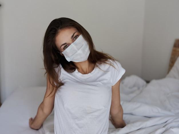 Jolie femme au masque médical est assise sur le lit avec la tête inclinée sur le côté