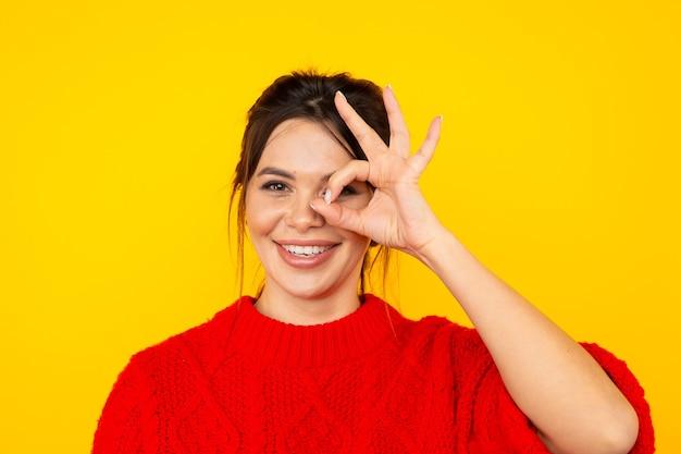 Jolie femme au pull rouge s'amusant dans le studio jaune.