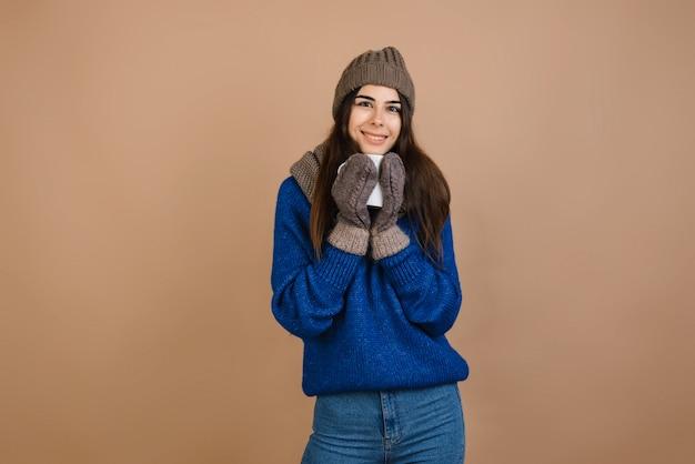 Une jolie femme au sourire éclatant portant un bonnet chaud, une écharpe, un pull et des mitaines tricotés tenant une tasse de thé chaud dans ses mains.