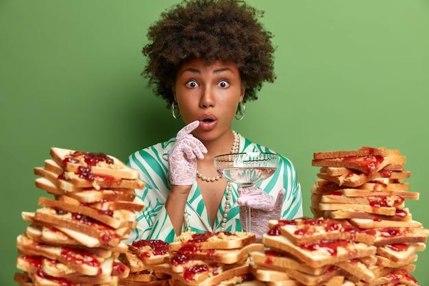 Jolie femme aux cheveux afro entourée de sandwiches en gelée de beurre de cacahuète