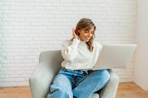 Jolie femme aux cheveux blonds ondulés assise sur un canapé à la maison travaillant sur un ordinateur portable