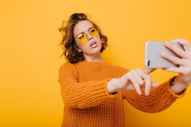 Jolie femme aux cheveux bouclés courts tenant le smartphone et en tapant un message devant un mur jaune