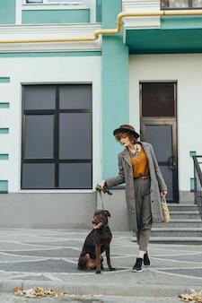 Jolie femme aux cheveux bouclés dans des vêtements élégants et un chapeau