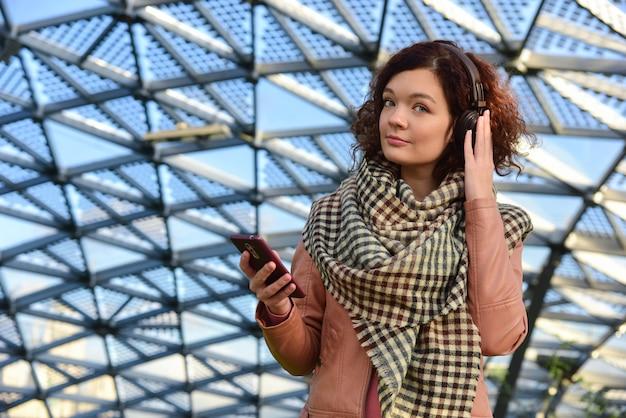 Jolie femme aux cheveux bouclés écoute de la musique en marchant.