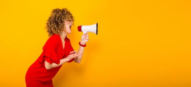 Jolie femme aux cheveux bouclés avec haut-parleur
